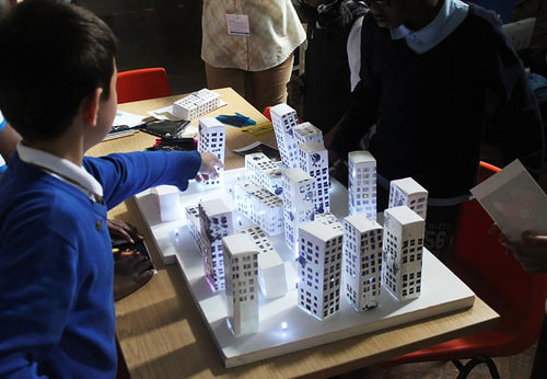Children playing with paper tower blocks and lights